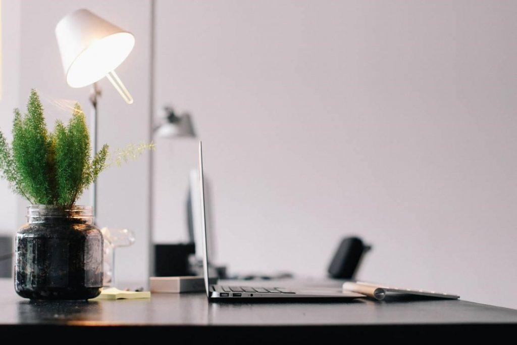 Grey Laptop on Black Wooden Desk